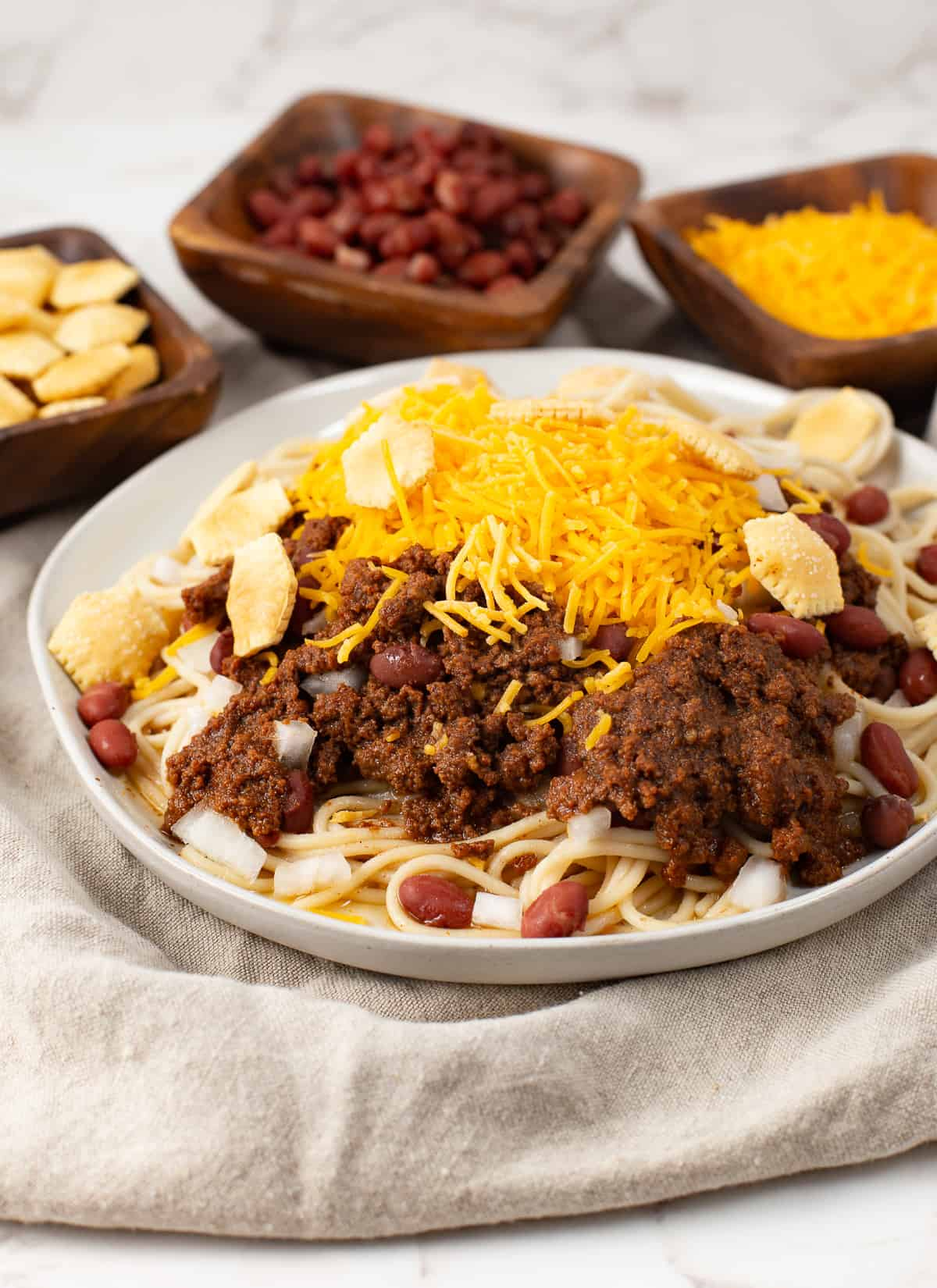 Authentic Instant Pot Cincinnati Chili on a plate with cheese and crackers on top