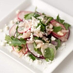 Radish Cilantro Salad with Goat Cheese is a fragrant spring salad of fresh radishes, cilantro and mild shallots tossed with a soy sauce vinaigrette then topped with creamy goat cheese.