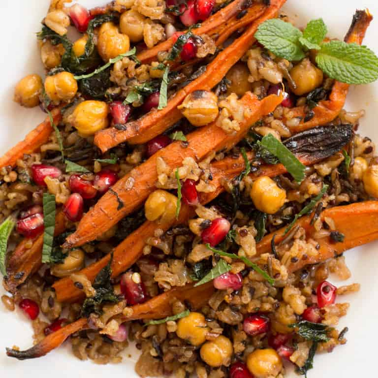 Roasted Carrots Chickpea Salad is tossed with a warm mix of seven grains, kale, and tart pomegranate seeds, drizzled with a sweet spiced maple dressing.