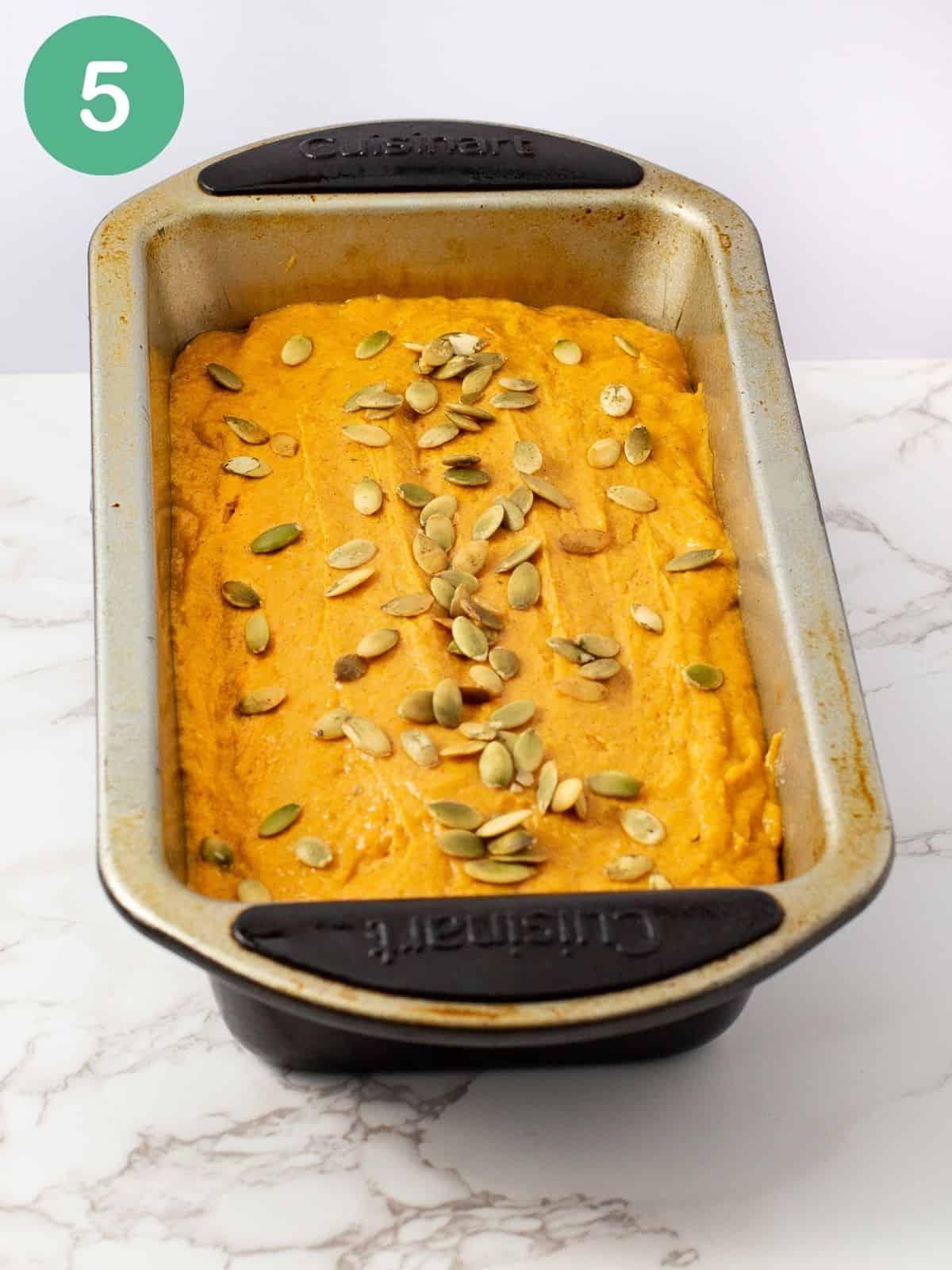 pumpkin bread batter in loaf pan with pumpkin seeds on top