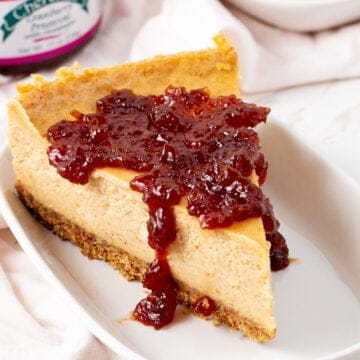 Creamy Pumpkin Vegan Cheesecake Recipe Tofutti with cranberry on top sitting on a plate
