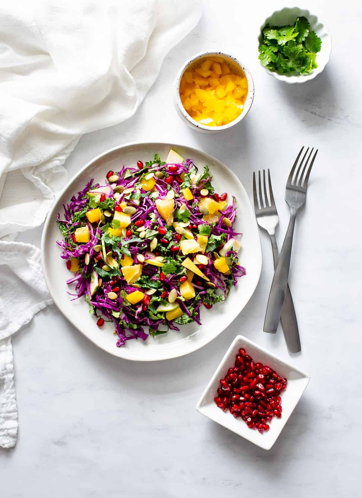 rainbow detox salad on a plate with ingredients in bowls