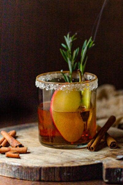 apple cider mocktail with rosemary lite and apple slice in glass