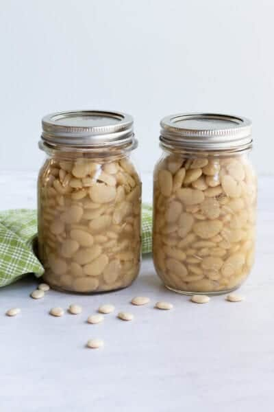 canning lima beans in two pint jars with dried beans on table
