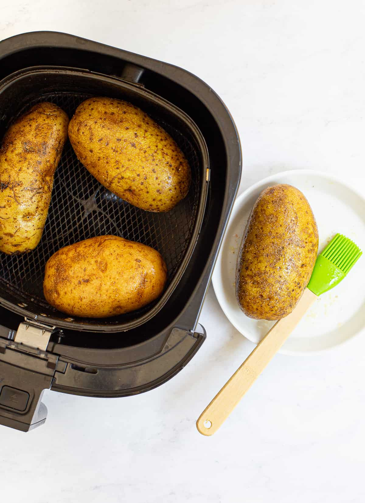Perfect Air Fryer Baked Potatoes Recipe covering potatoes with olive oil