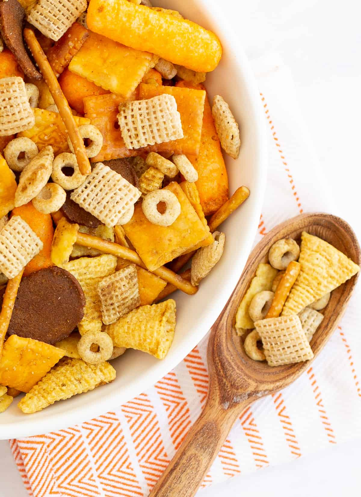 Easy & Unique Slow Cooker Chex Mix Recipe in a bowl with a serving spoon full
