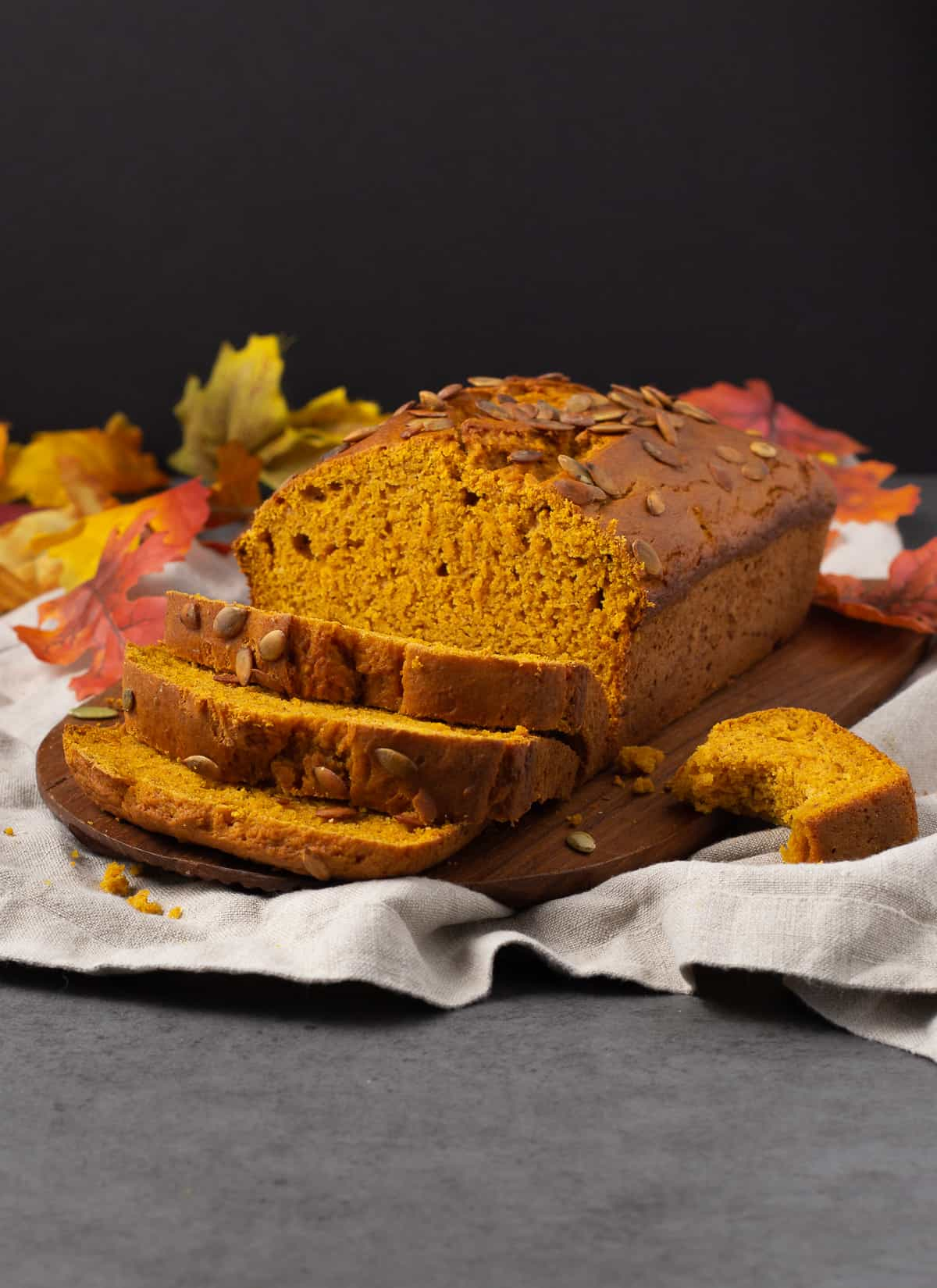 loaf of pumpkin bread sliced and pumpkin seeds on top