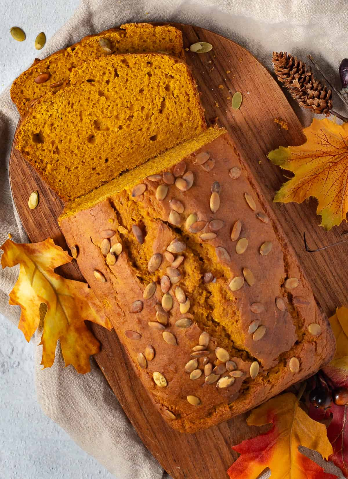 pumpkin bread with slice and pumpkin seeds on top