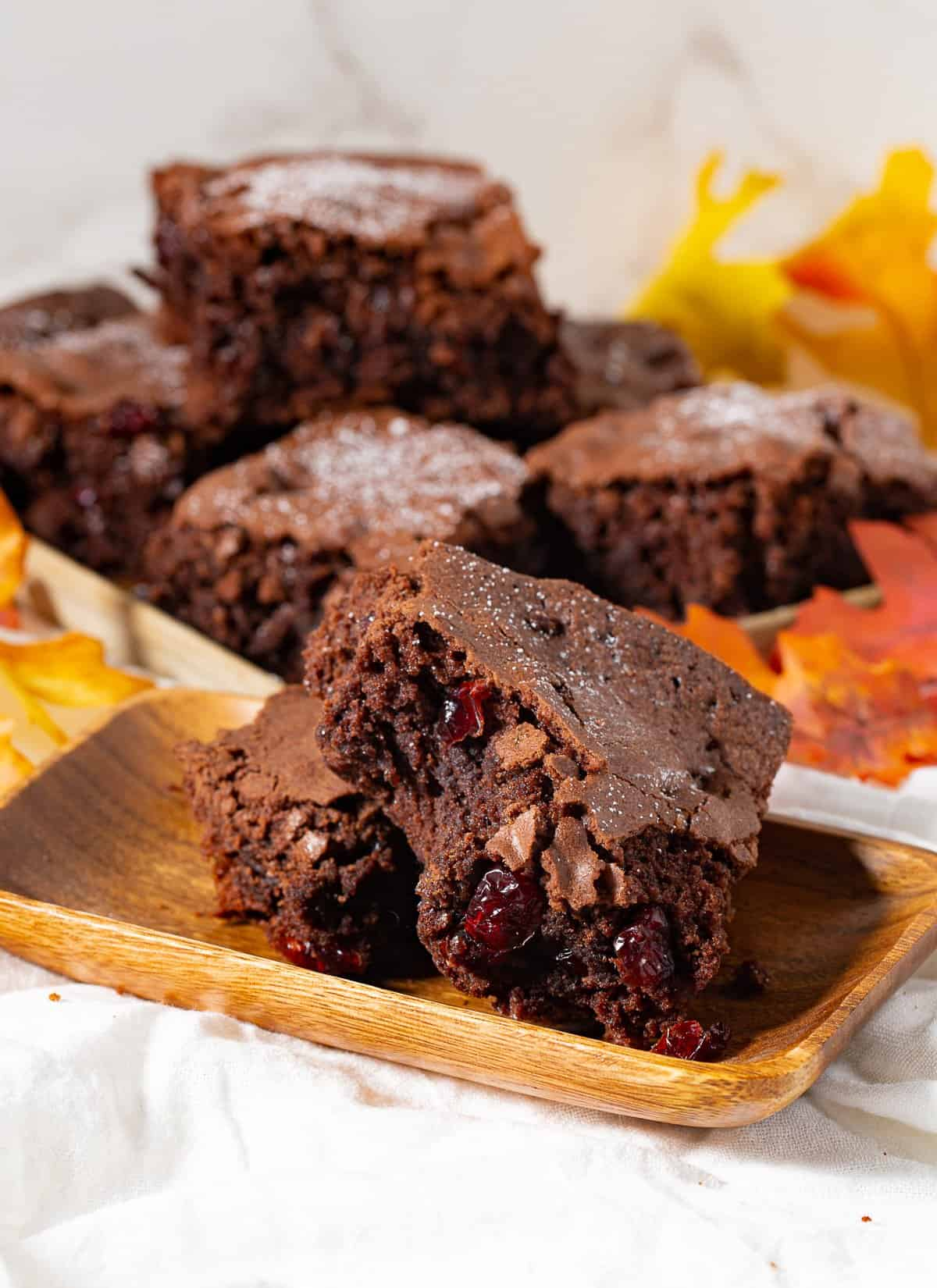 Thanksgiving Cranberry Chewy Brownies on wood plate with fall leaves around